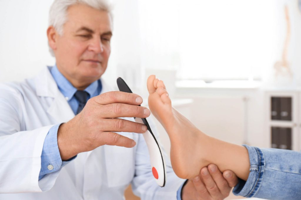 Male orthopedist fitting insole on patient's foot in clinic